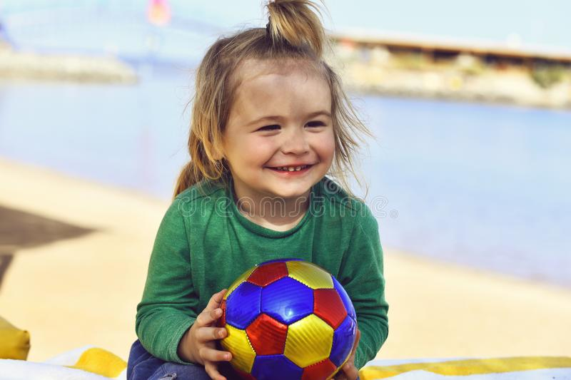 Little smiling boy kid with long blond hair holding ball royalty free stock photo