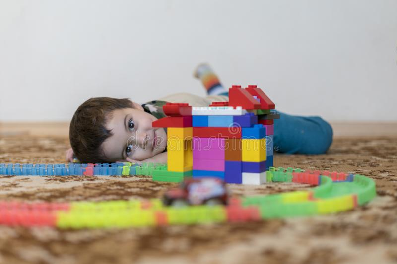 little smiling boy playing with constructor toy. Boy playing intellectual toys stock photography