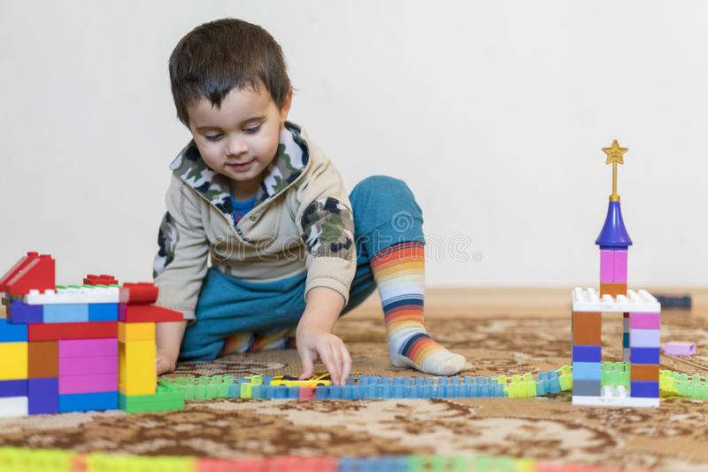 little smiling boy playing with constructor toy. Boy playing intellectual toys stock image