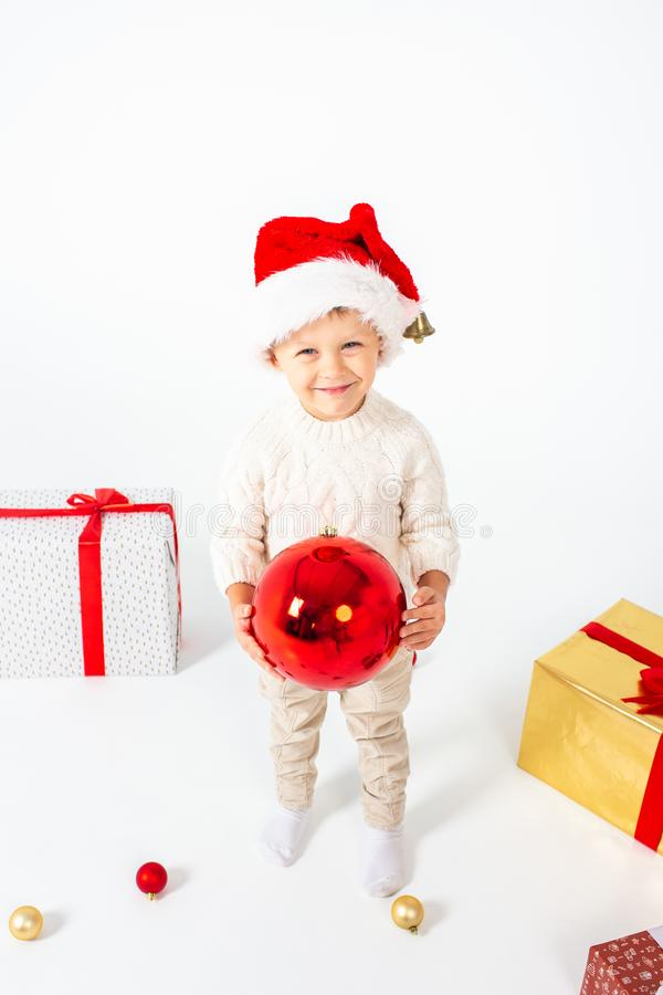 Little boy standing between gifts and holding big red Christmas ball in hands. Isolated on white background. Holidays, christmas, stock images