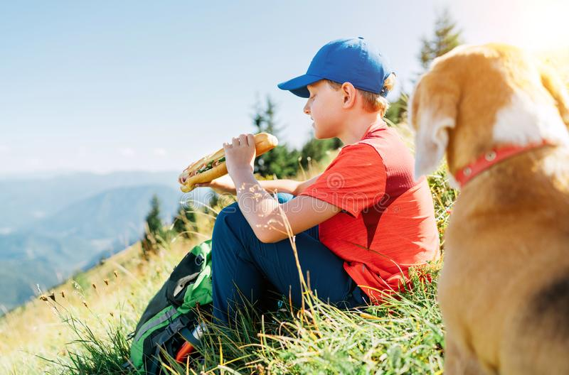 Little smiling boy weared baseball cap enjoying a huge baguette sandwich and his beagle dog friend watching it during a mountain stock photos