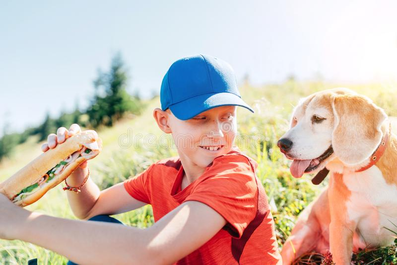Little smiling boy weared baseball cap with a huge baguette sandwich with his beagle dog friend during a mountain hiking resting royalty free stock image