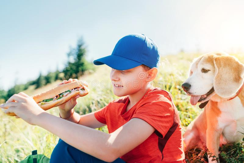 Little smiling boy weared baseball cap with a huge baguette sandwich with his beagle dog friend during a mountain hiking resting royalty free stock photos