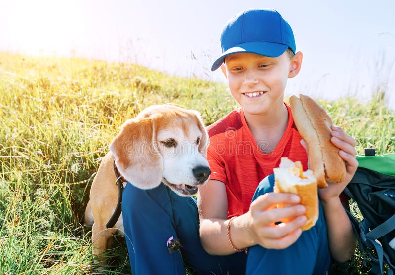 Little smiling boy weared baseball cap sharing a huge baguette sandwich with his beagle dog friend during a mountain hiking stock photos