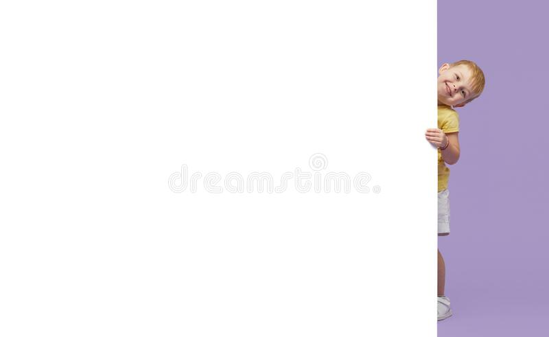 Little smiling child standing behind a white blank panel isolated against purple background. Peeking out from behind a banner, emp stock photos
