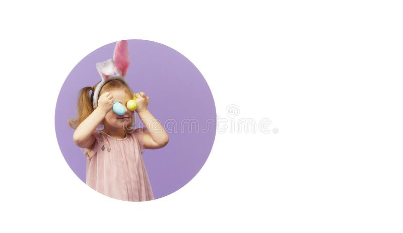 Little smiling child standing behind a white blank panel isolated against purple background. Peeking out from behind a banner, emp stock photography