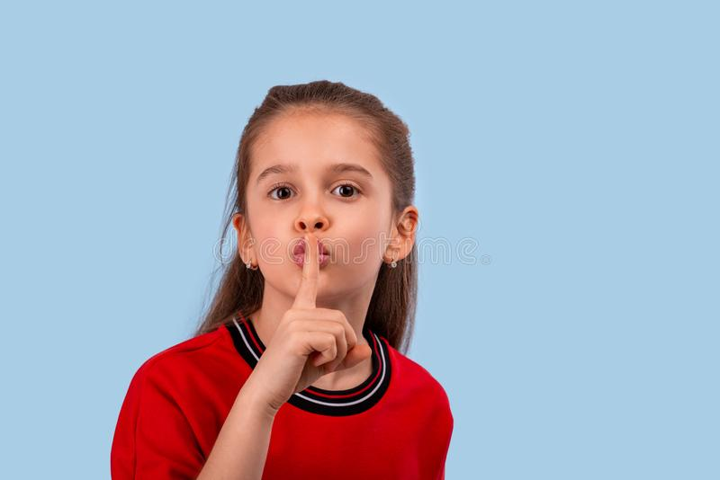 A little smiling girl  asks for silence or not to tell a secret while keeping her forefinger at her lips stock images