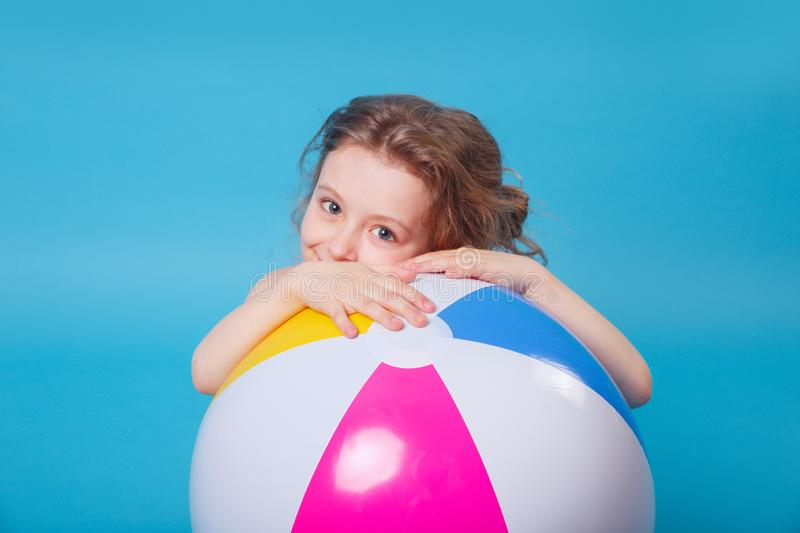 Little smiling girl with big inflatable ball on blue background stock images
