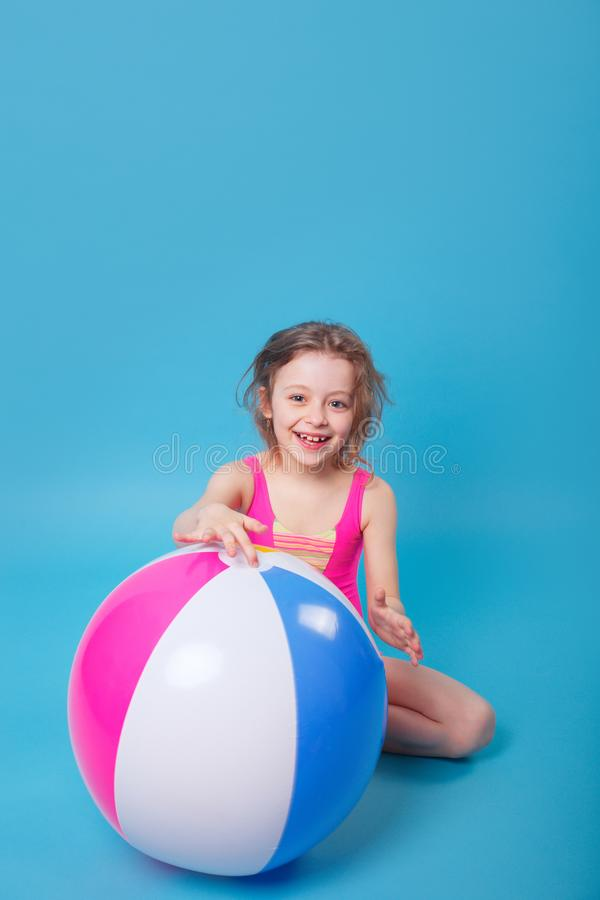 Little smiling girl with big inflatable ball on blue background royalty free stock image