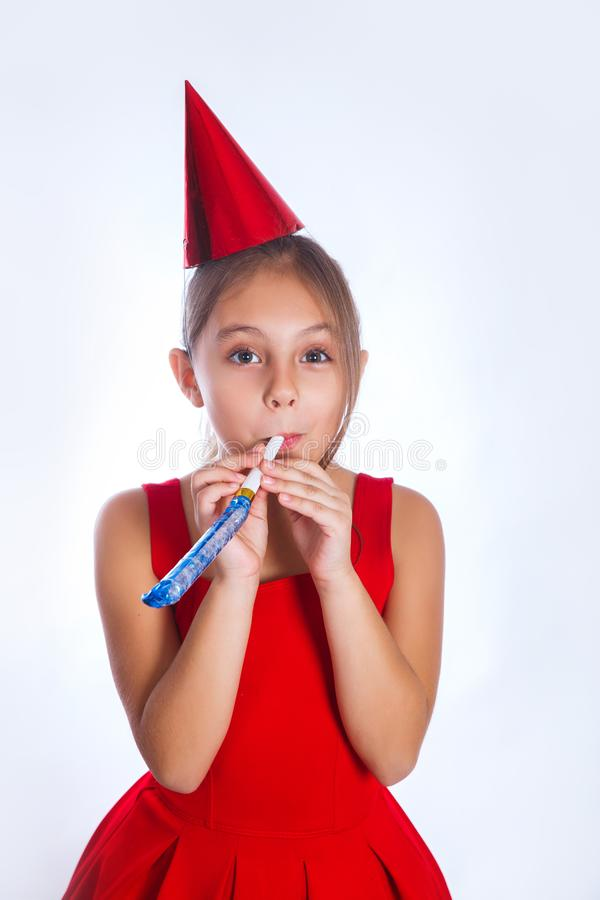 Little smiling funny girl with birthday hat and whistle on white background. Little smiling girl with birthday hat and whistle on white background. Celebration royalty free stock photo