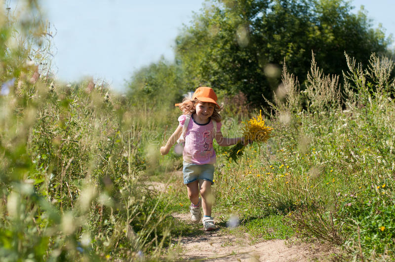 A little smiling girl with a bouquet of field summer flowers running along the path of a forest. A photo of a little smiling girl with a bouquet of field summer stock photo