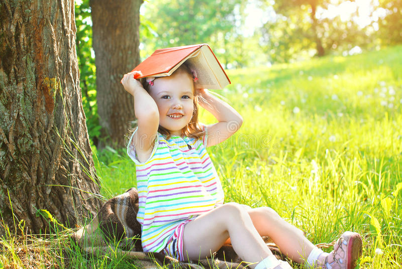 Little smiling girl child with book playing on the grass. In sunny summer day royalty free stock photo