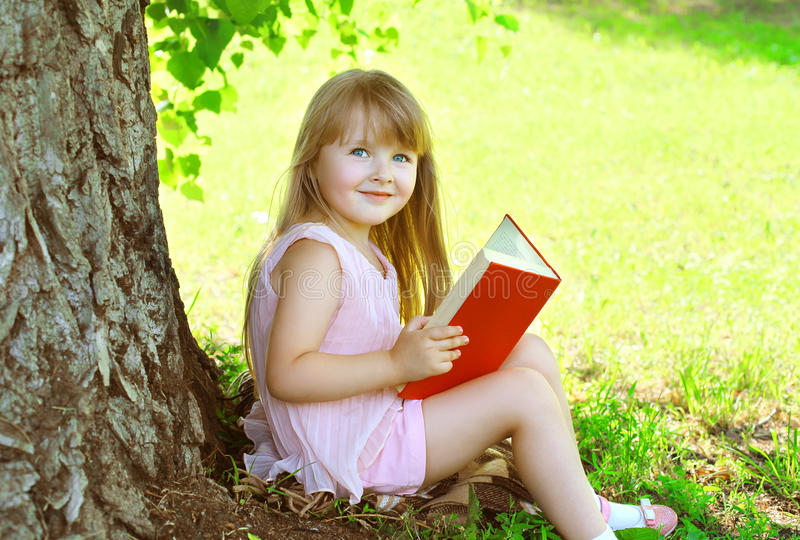 Little smiling girl child reading a book on the grass near tree. In summer park royalty free stock photo