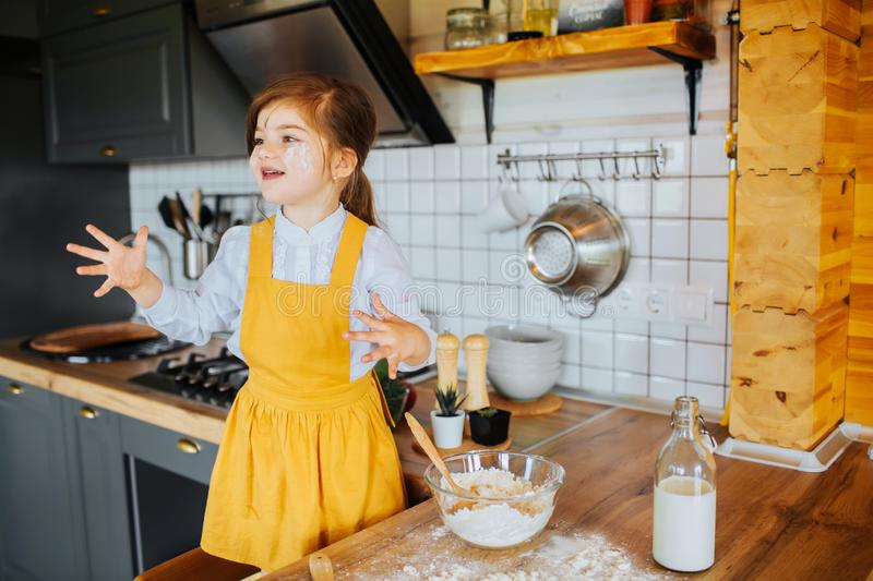 Little happy girl playing around in the kitchen. stock images