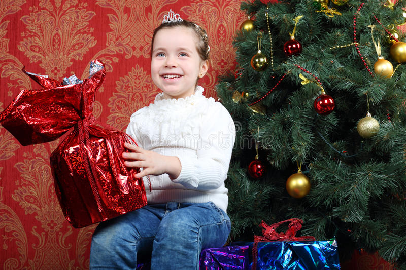 Little smiling girl holds gift near Christmas tree. And looks up at home royalty free stock photos