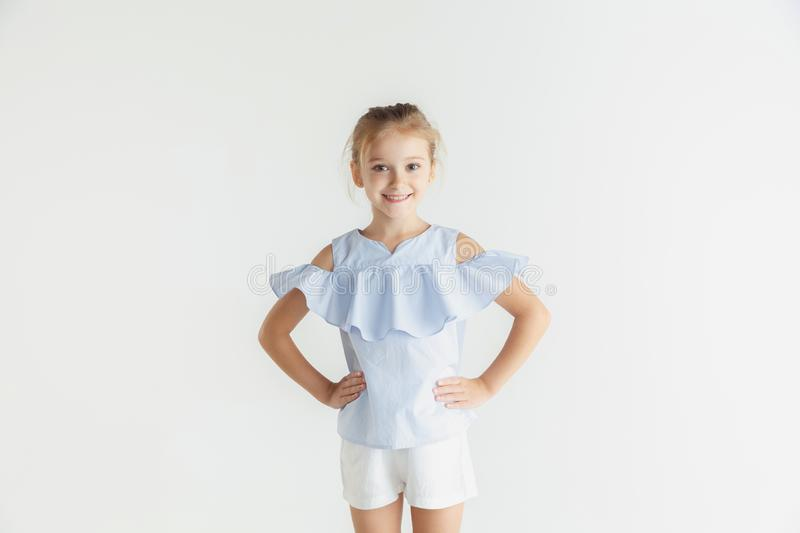 Little smiling girl posing in casual clothes on white studio background stock photo