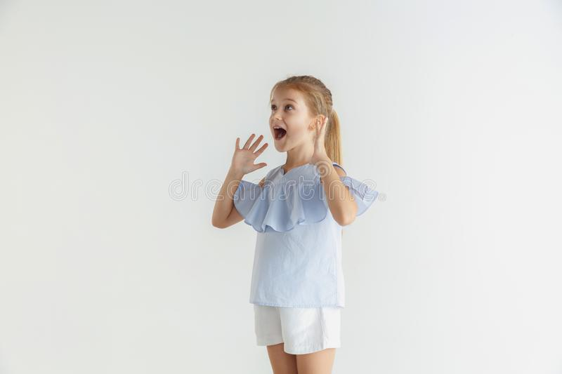 Little smiling girl posing in casual clothes on white studio background. Stylish little smiling girl posing in casual clothes isolated on white studio background royalty free stock photos