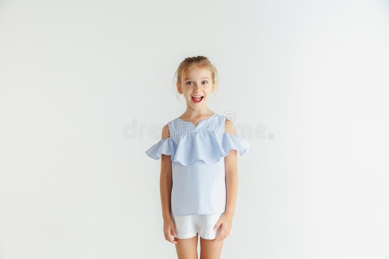 Little smiling girl posing in casual clothes on white studio background. Stylish little smiling girl posing in casual clothes isolated on white studio background stock images