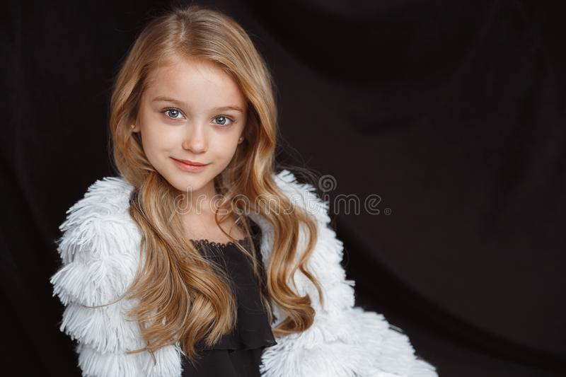 Little smiling girl posing in white outfit on black studio background. Stylish little smiling girl posing in white outfit isolated on black studio background stock photography