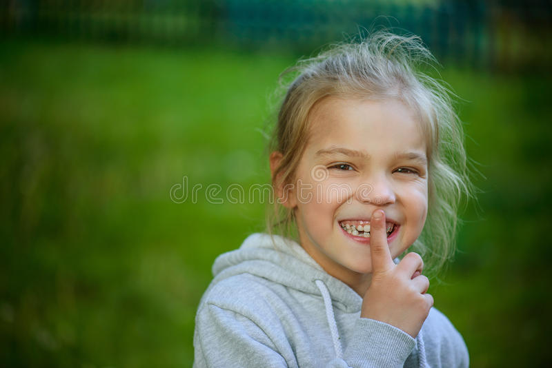 Little smiling girl in puts forefinger to lips royalty free stock image