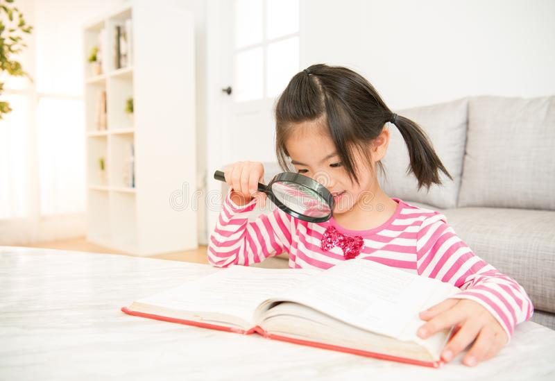 Little smiling girl reading a book stock image