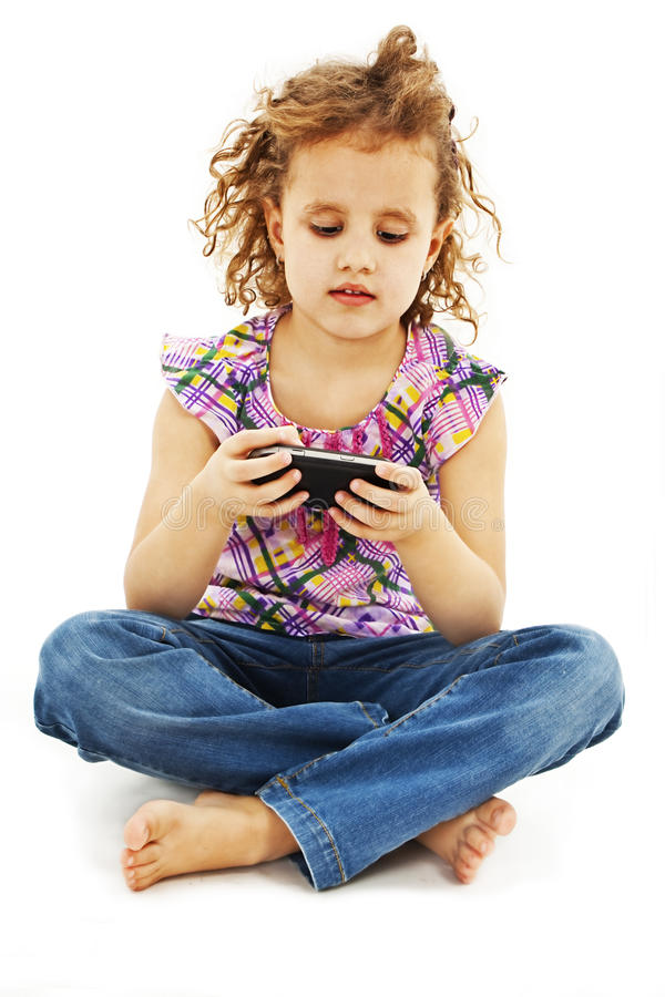 Little smiling girl reading sms on your cell phone. Isolated on white background royalty free stock image