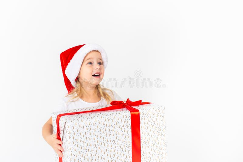 Little smiling girl in santa helper hat holding white gift with red ribbon on white isolated background. Christmas, winter, stock images