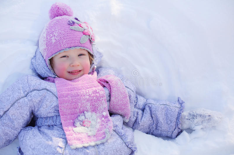 Little smiling girl in scarf and hat lies on snow at winter stock photo