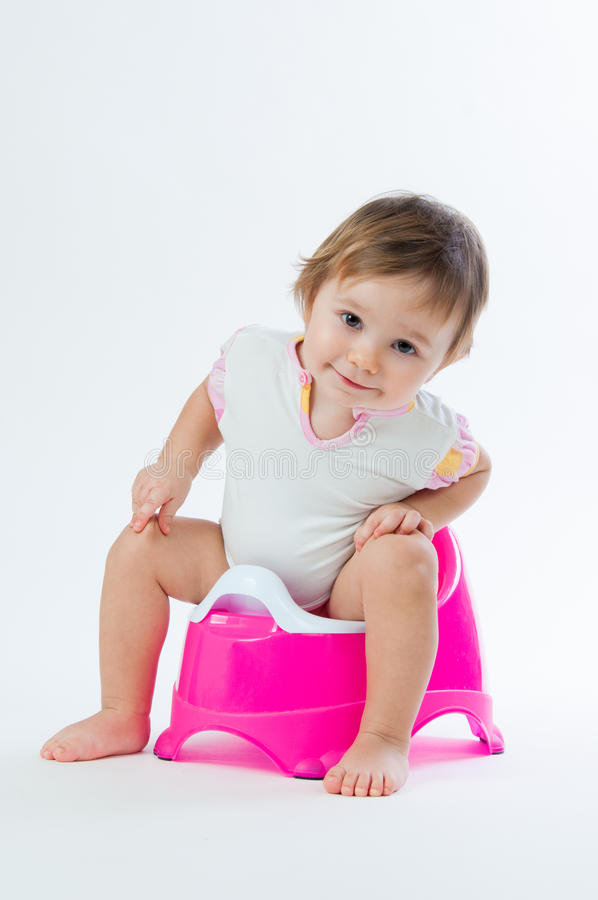 Little smiling girl sitting on a pot. on white background. Little smiling girl sitting on a pot. on white background royalty free stock photos