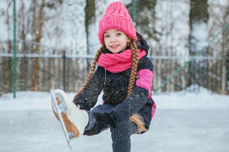 Little smiling girl skating on ice in pink wear. winter royalty free stock photo