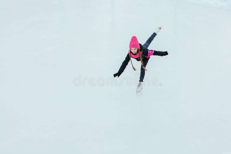 Little smiling girl skating on ice in pink wear. winter royalty free stock images