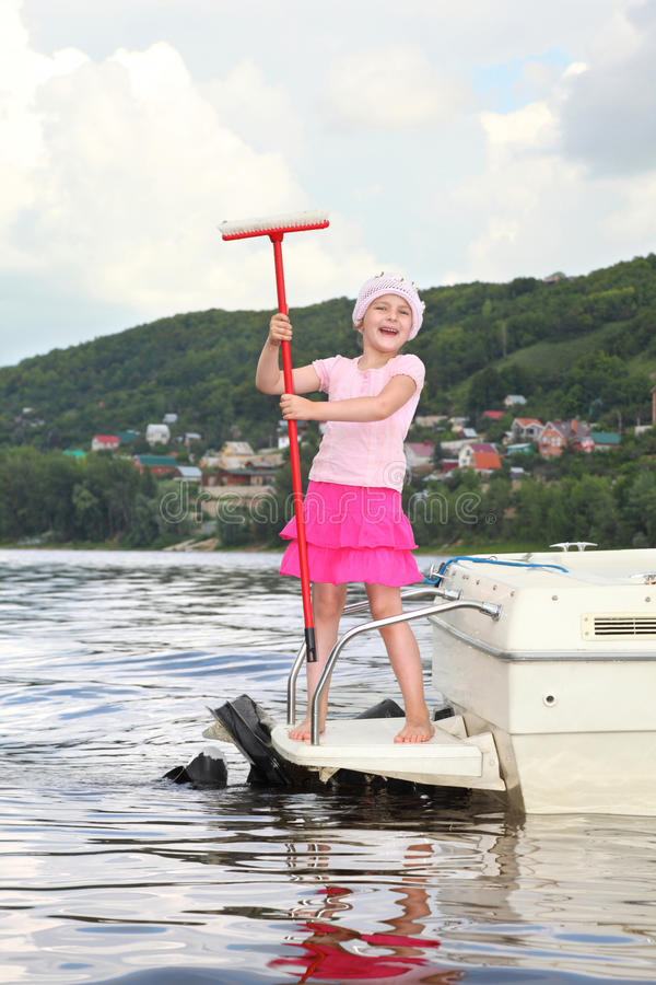 Little smiling girl stand on ladder of cutter stock image