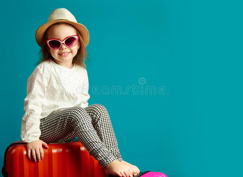 Little smiling girl in straw hat and sunglasses sitting on suitcases, portrait of beautiful child going on a journey royalty free stock image
