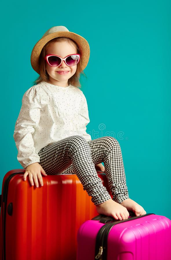 Little smiling girl in straw hat and sunglasses sitting on suitcases, portrait of beautiful child going on a journey royalty free stock photos