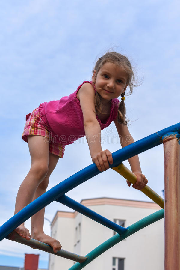 A little smiling girl using the sports equipment in a playground of an apartment house& x27;s court yard. A photo with a little smiling girl using the sports royalty free stock photography