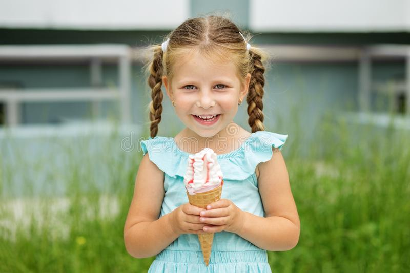 Little smiling girl is walking outdoors and eating ice cream. The concept of childhood, lifestyle, food, summer. Little smiling girl is walking outdoors and stock images