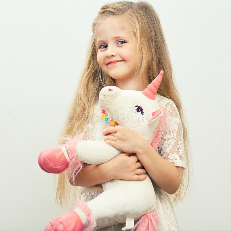 Little smiling girl with white unicorn toy. stock photography