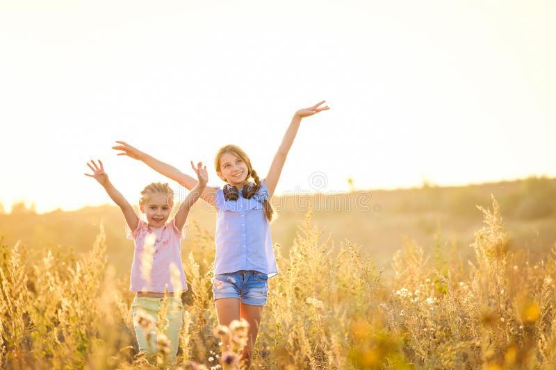 Little smiling girls stand with joyfully raised hands royalty free stock image