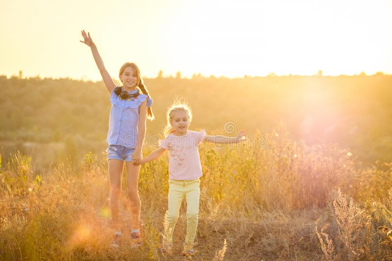 Little smiling girls stand with joyfully raised hands stock image