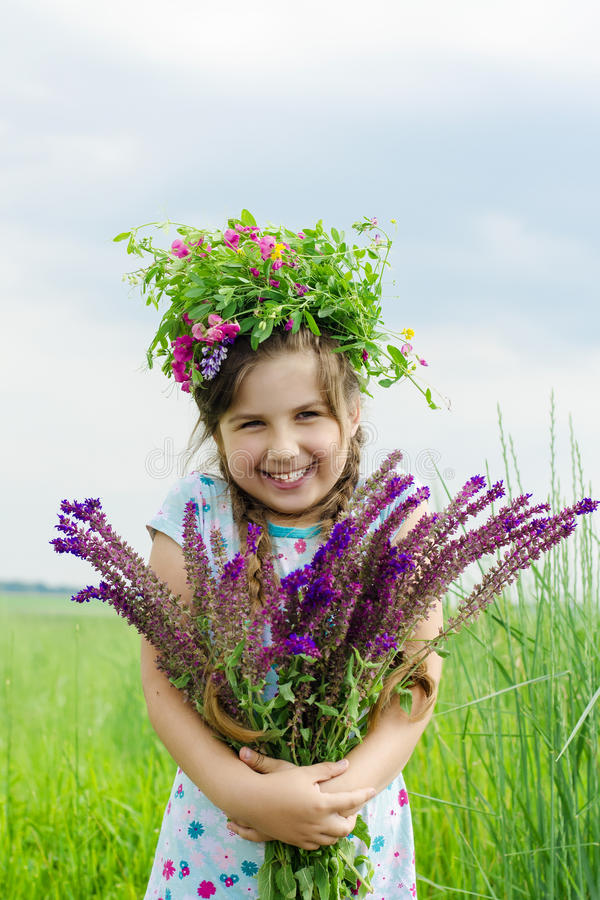Little smiling happy girl with a bouquet of wild flowers and a wreath on his head among green meadow royalty free stock photography
