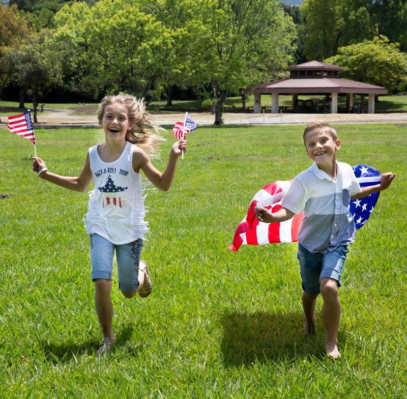 Adorable little girl and boy run on bright green grass holding american flag outdoors on beautiful summer day stock images
