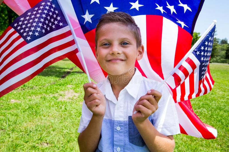 Adorable little boy holding american flag outdoors on beautiful summer day. Little smiling patriotic girl with long blond hair, red head band bandana and royalty free stock images