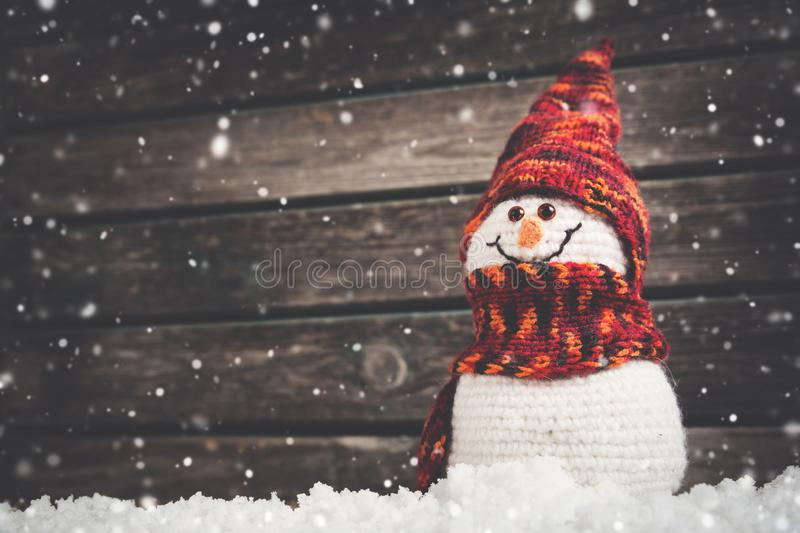 Little snowmans on soft snow on wooden background stock photography