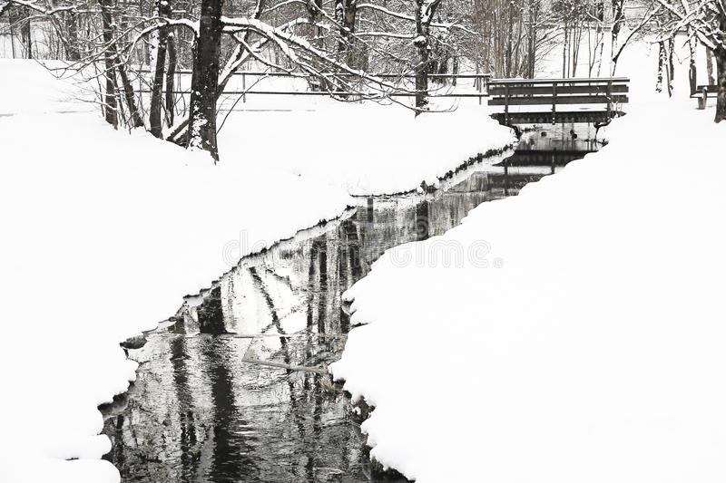 Little snowy creek and bridge at winter time. In black and white royalty free stock photos