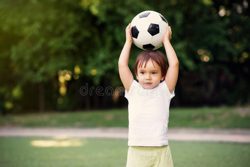 Little soccer player at football field outdoors: toddler boy holding ball above head ready to throw it in sunny day. Summer. Outdoors fun and sports for kids stock photography