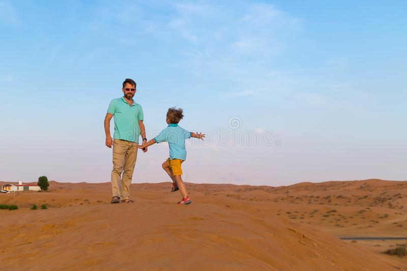 little son is runs on a meeting to the father on dunes in the hot desert stock photos