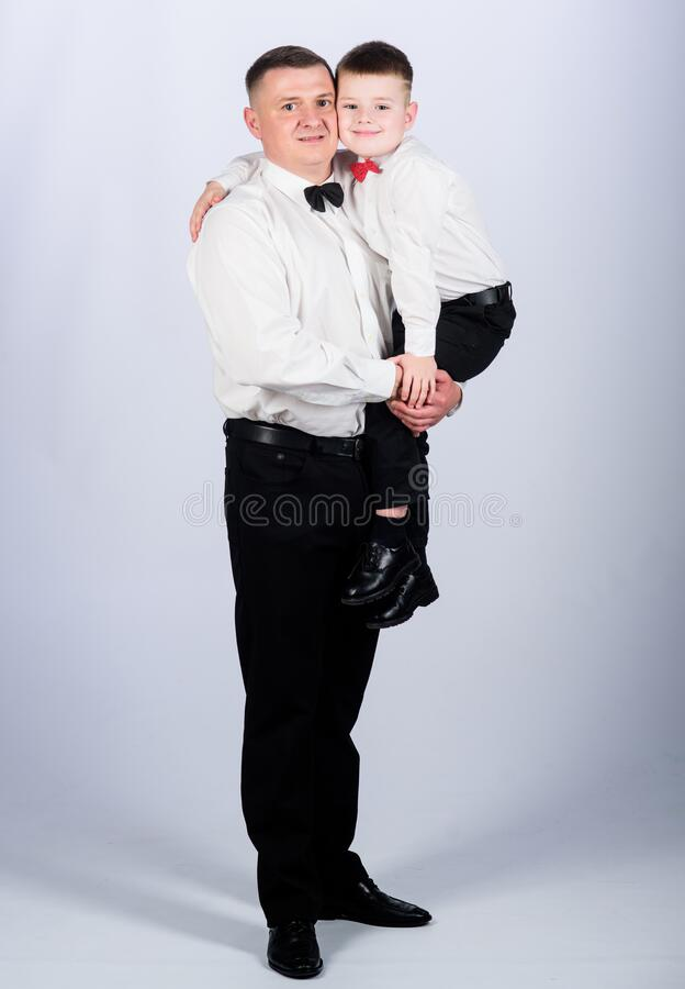 Little son following fathers example of noble man. Family holiday. Relations of dad and son. Gentleman upbringing. Father carry hug son formal clothes outfit stock images