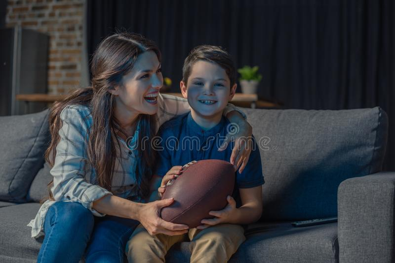 Little son and his beautiful mother laughing while sitting on couch and watching an american stock photo