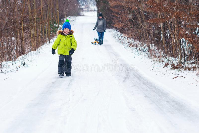 Little son with mother sliding in the snow in winter park. Happy young family enjoying a sledge ride. Winter holidays. Young happy stock images