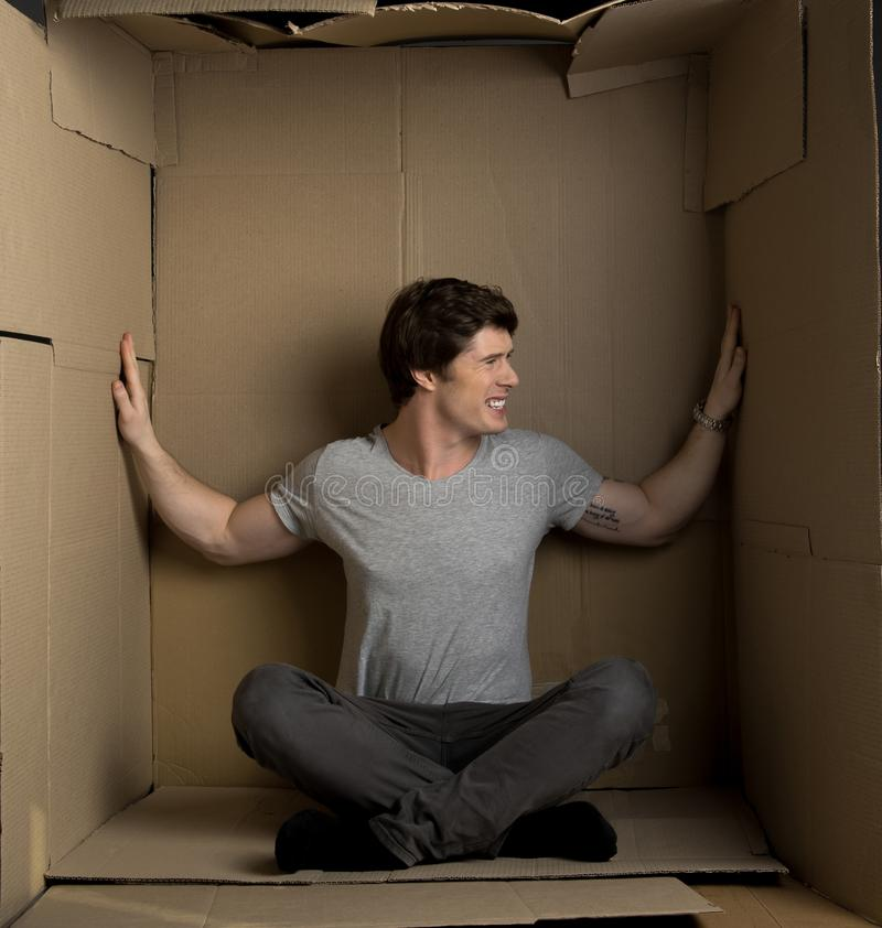 Young man is pressuring on walls inside cardboard box. Little space concept. Full length of depressed guy is living in small carton room. He is feeling stock photos